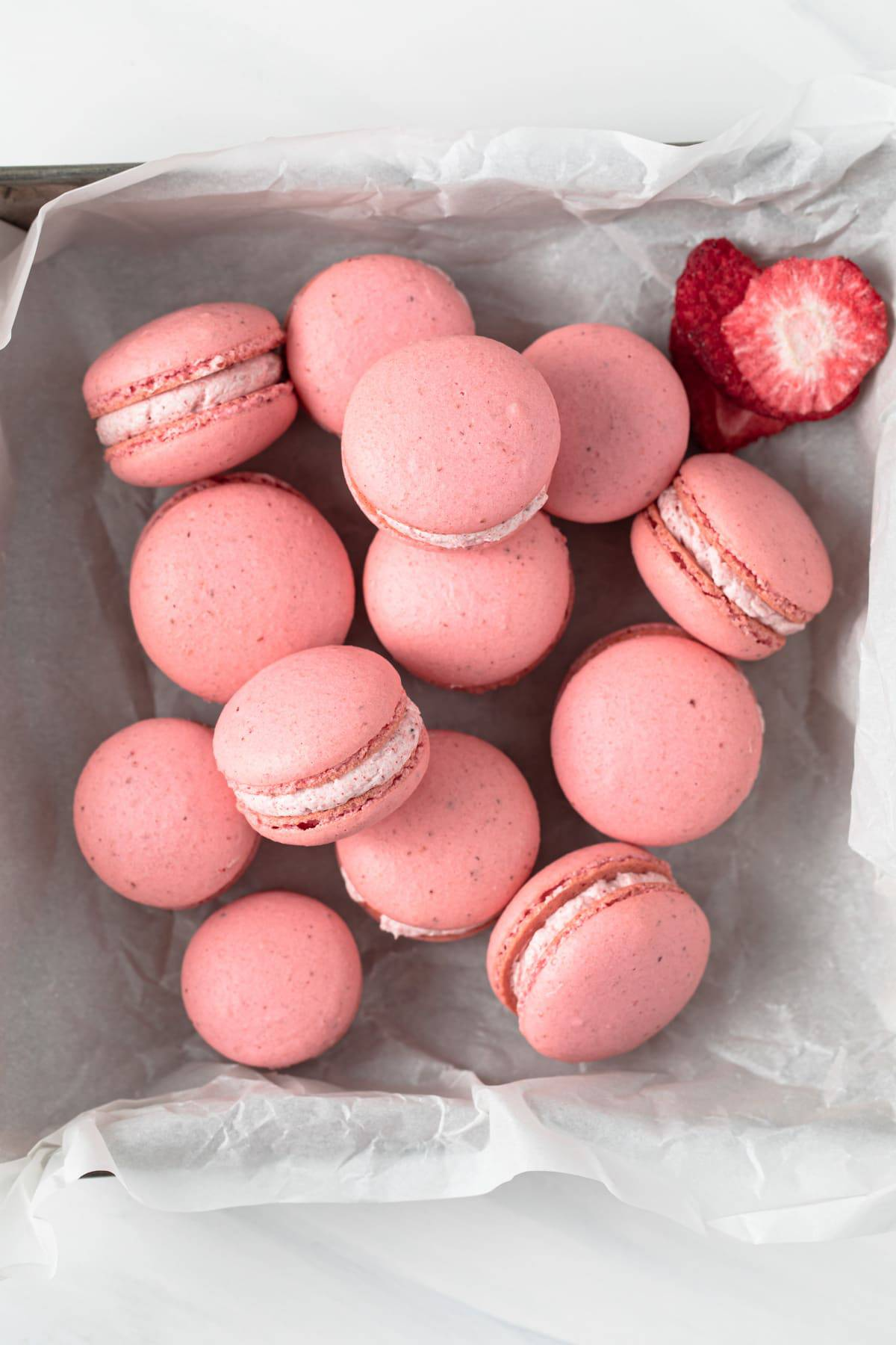 overhead of strawberry French macarons scattered in a square baking pan