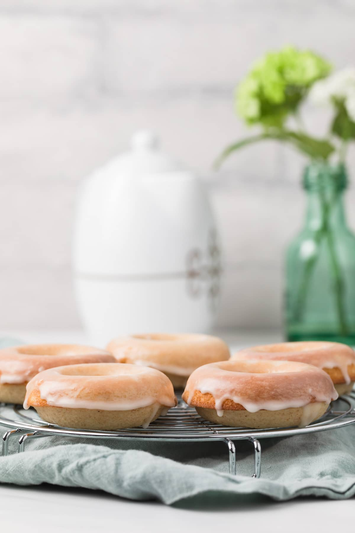 baked donuts arranged in single layer on round metal rack with blue napkin underneath and white tea pot next to glass flower vase