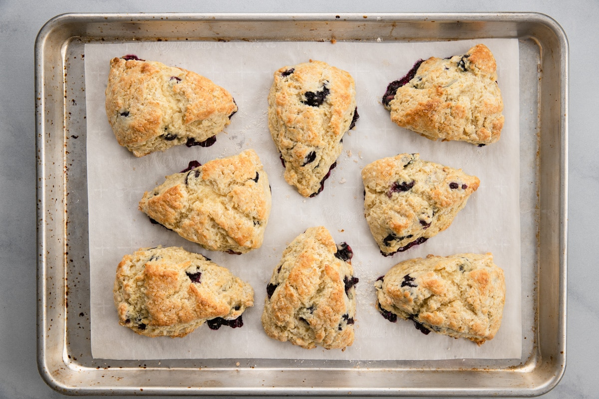overhead of baked blueberry scones on baking sheet lined with white parchment paper