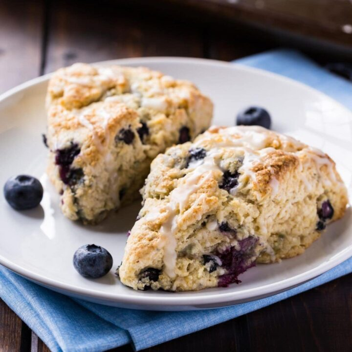 Two blueberry scones on a white plate with a baking sheet in the background.