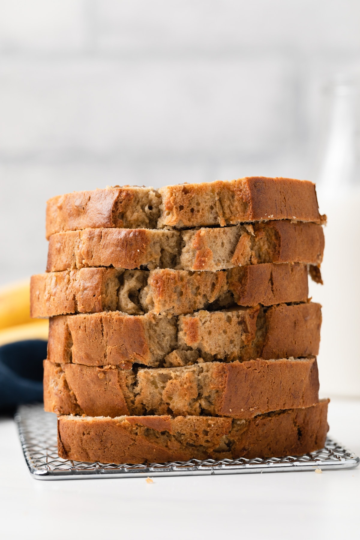 side view of six slices of easy banana bread stacked on wire rack with bananas and jar of milk in background