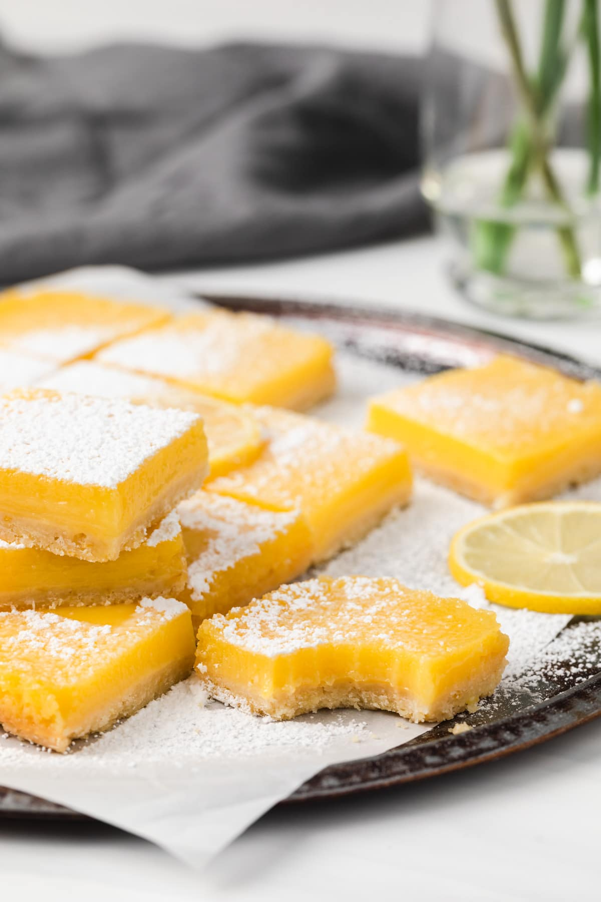 lemon bars on a parchment lined baking tray with a bite taken out of one