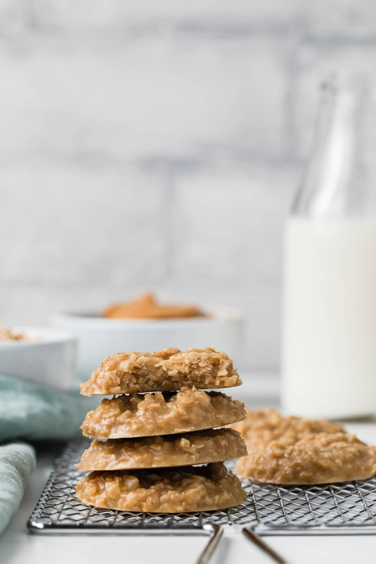 stack of four peanut butter no-bake cookies on a wire rack with a bowl of peanut butter and jar of milk behind it