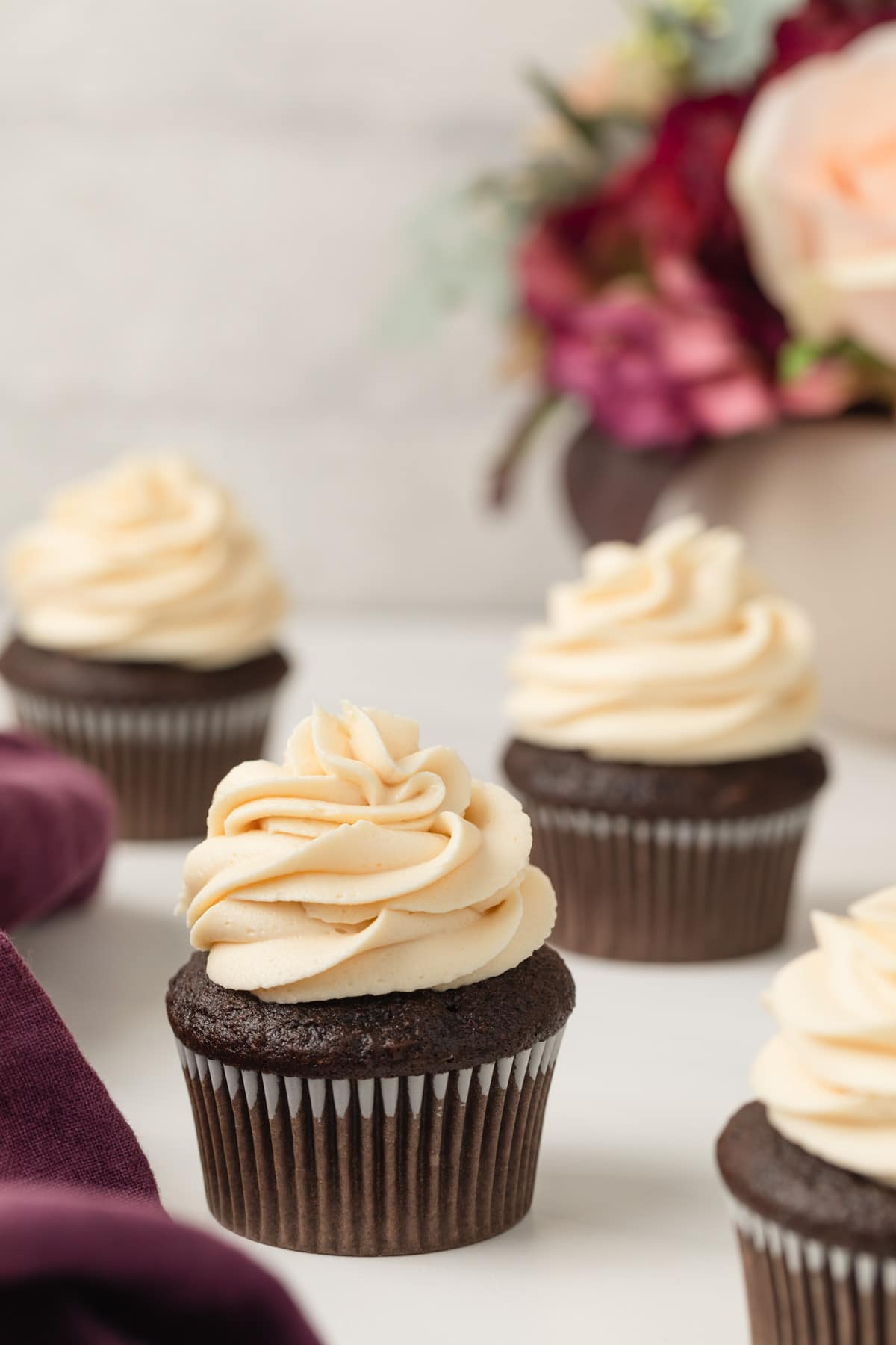 four chocolate cupcakes topped with a swirl of salted caramel frosting with purple cloth to the side and colorful flowers in the background
