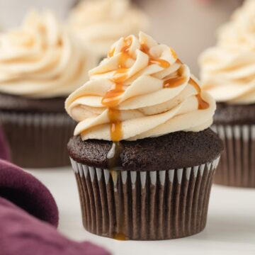salted caramel frosting swirled on top of a chocolate cupcake with a drizzle of caramel sauce