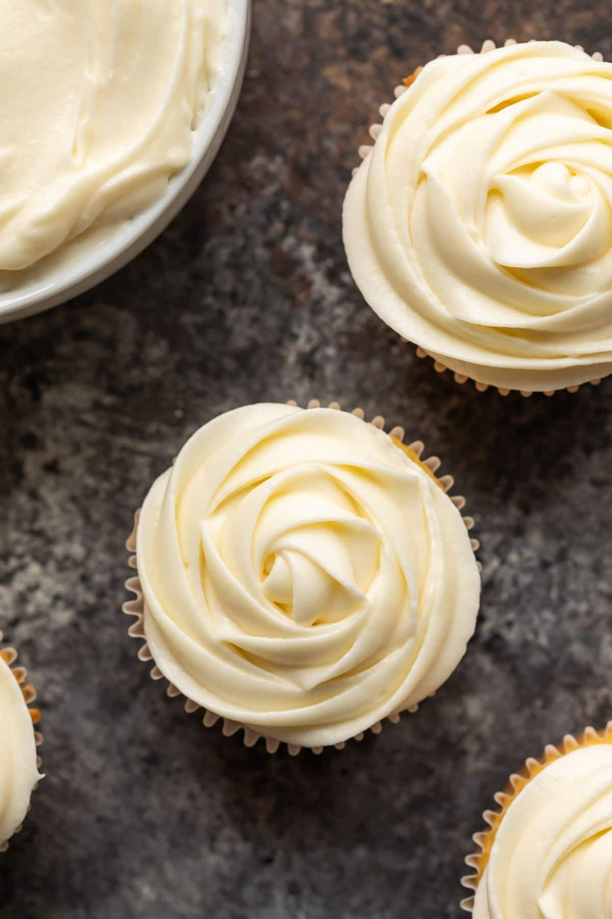 Close up overhead view of cream cheese frosting swirled over yellow cupcakes