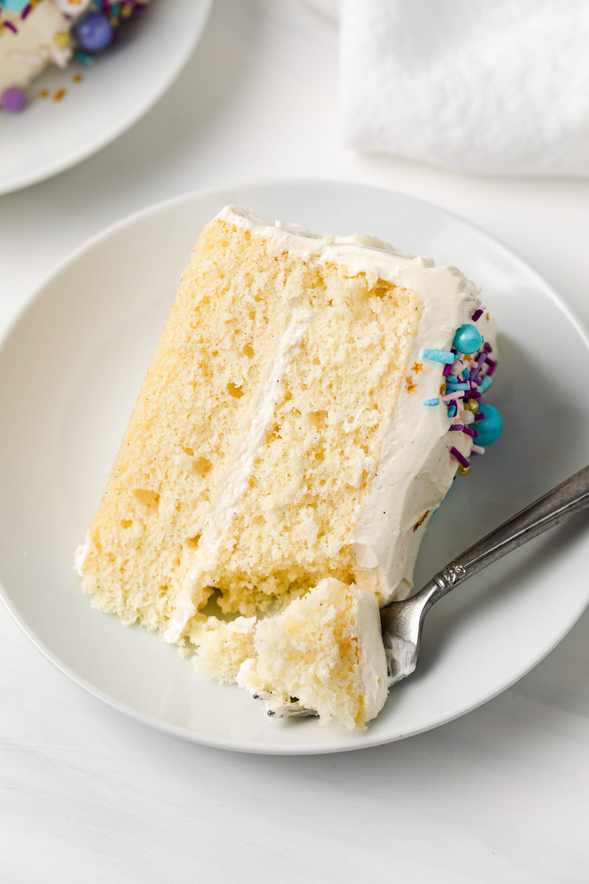 angled view of a slice of moist vanilla cake on white plate with a fork taking out a bite