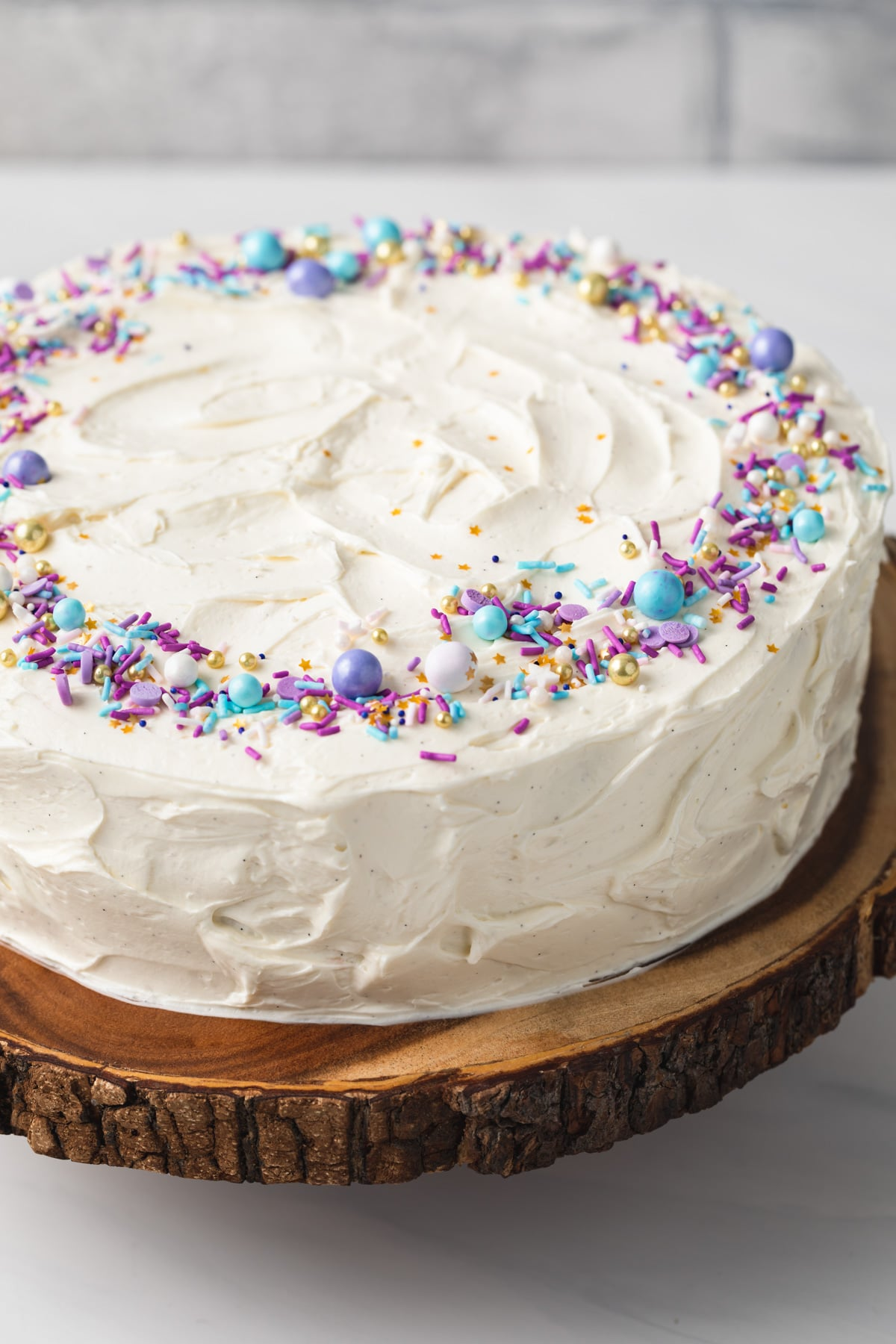 angled view of vanilla cake with colorful sprinkles on a wooden cake stand