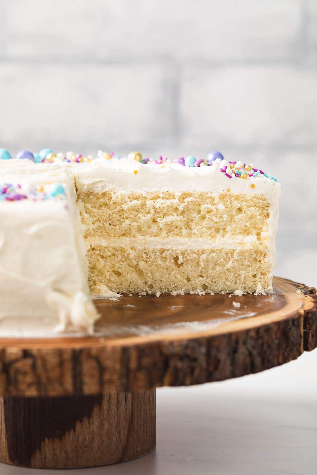 side view of a moist vanilla cake on wooded cake stand with a slice cut out