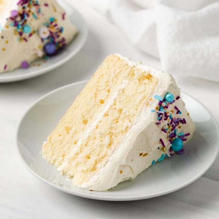 side view of slice of moist vanilla cake with colorful sprinkles on white plate