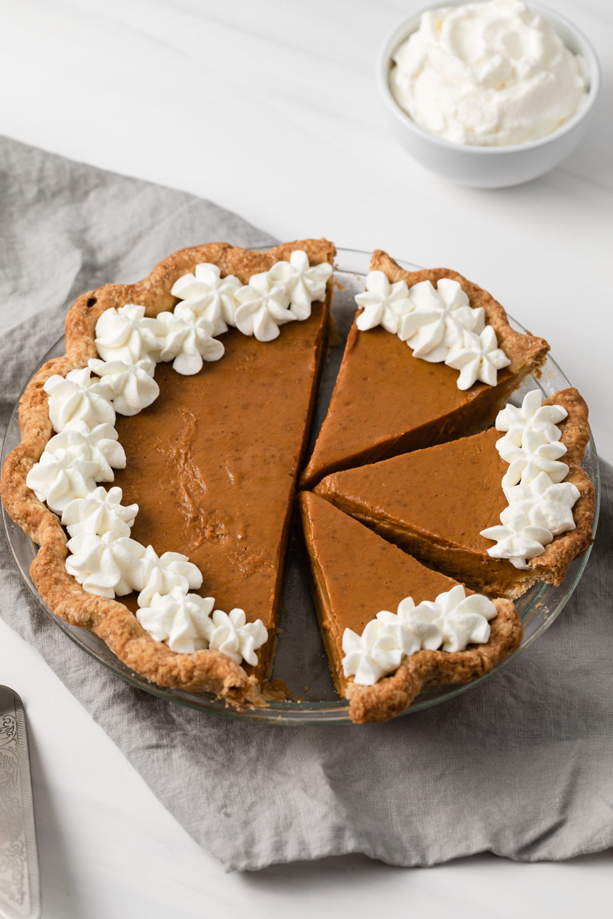angled view of pumpkin pie with slices cut