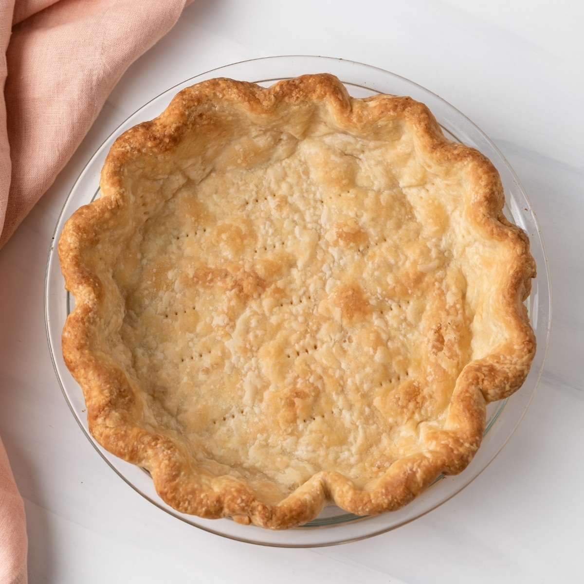 overhead of blind baked pie crust in glass pan with peach colored napkin