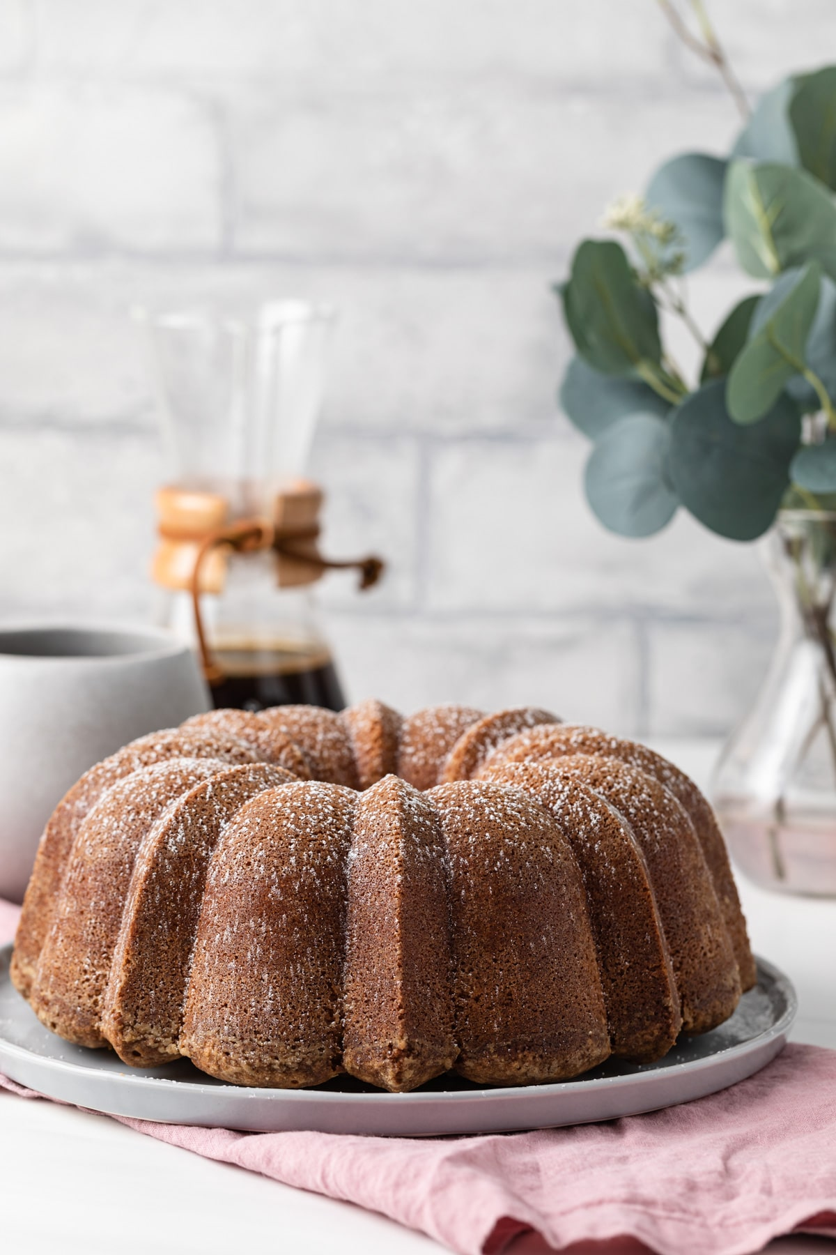 front view of whole pound cake on grey plate over a pink napkin with coffee and plant in background