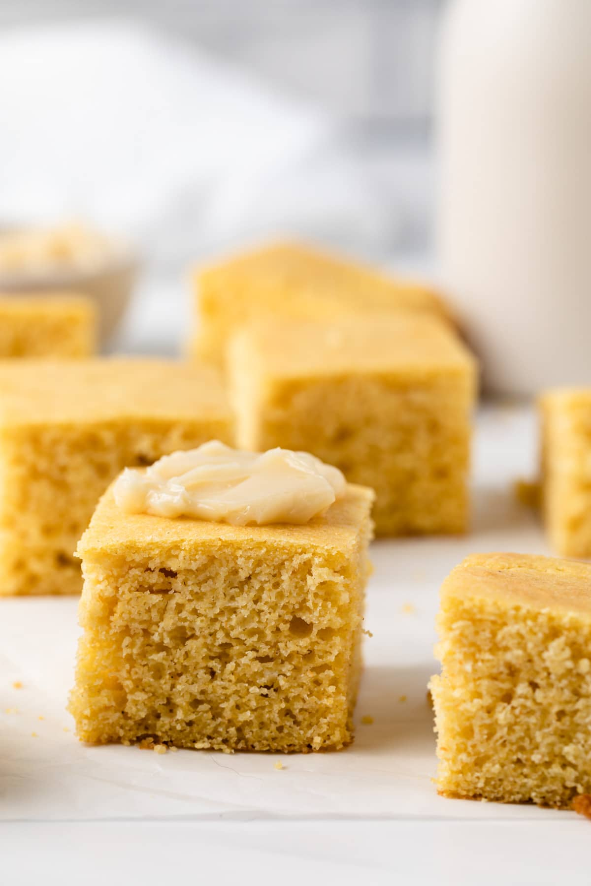 front view of southern cornbread squares with butter smeared on top of one