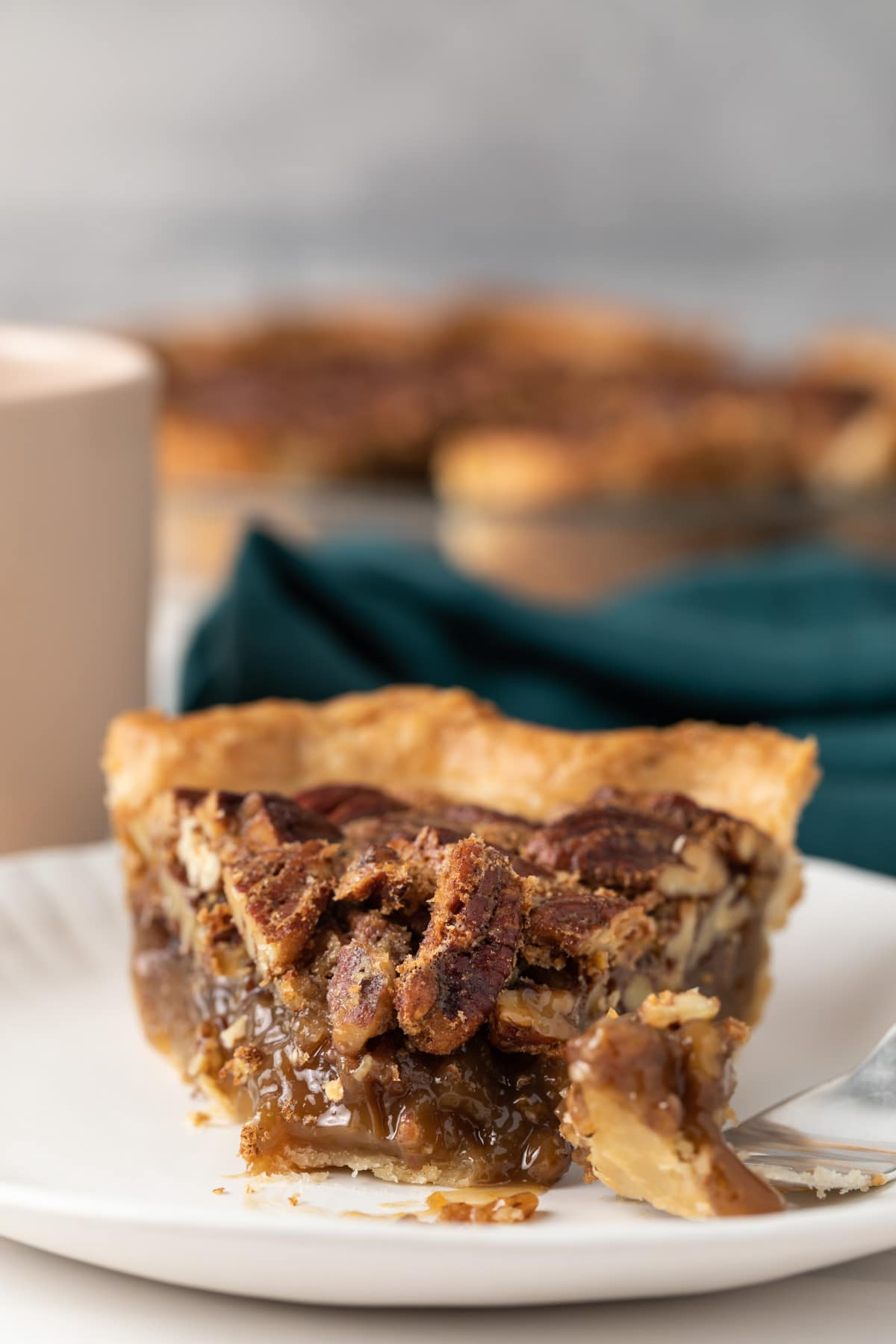 slice of pecan pie with fork taking a bite out