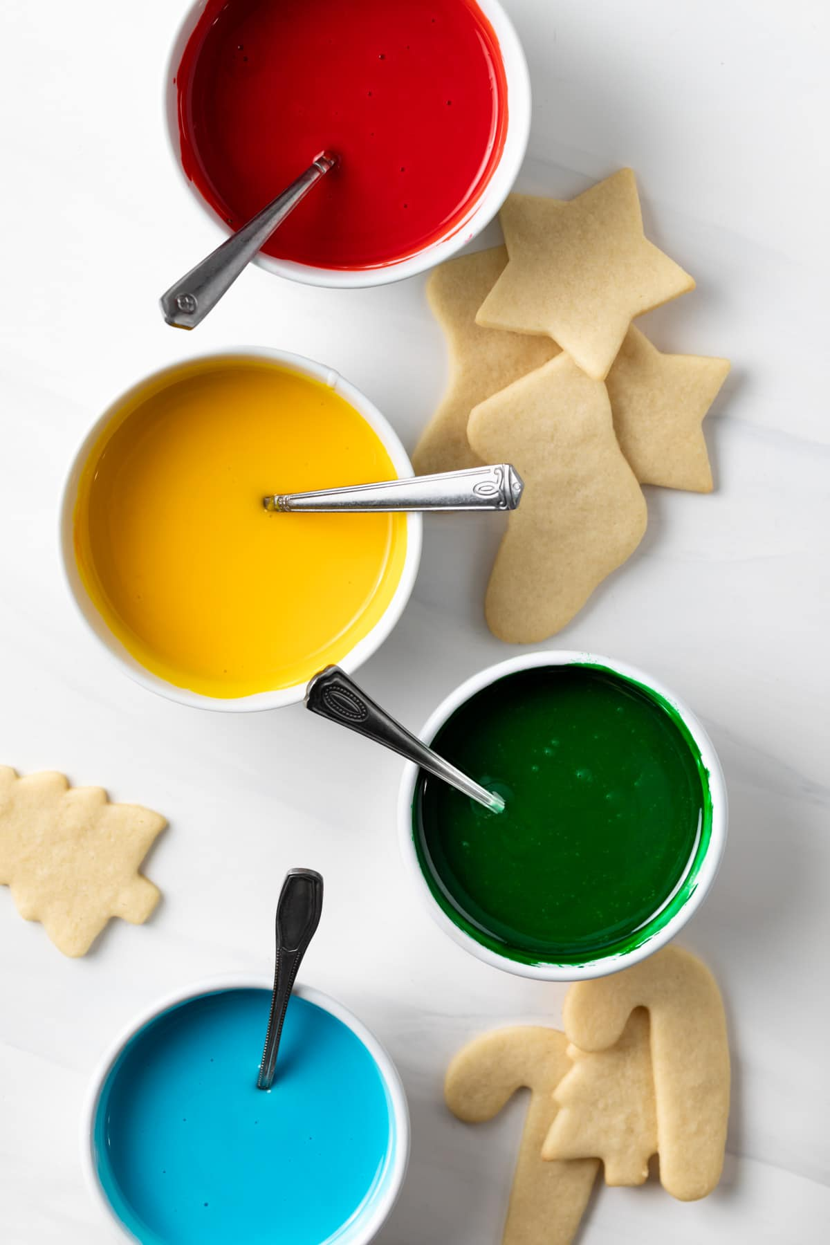 bowls of red, yellow, green, and blue icing with sugar cookies
