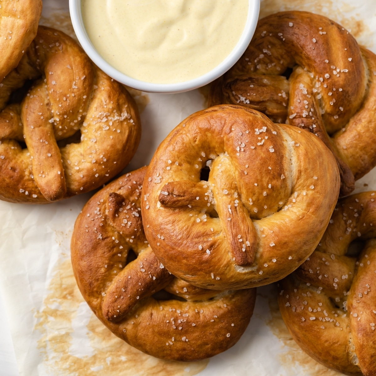 overhead of soft pretzels on a baking sheet with white bowl of mustard sauce