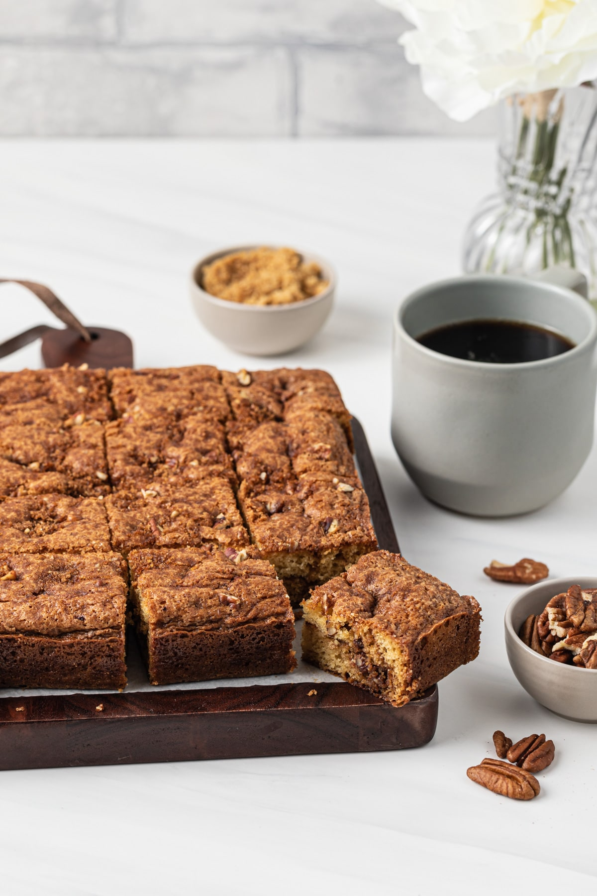 sliced coffee cake on wooden board with cup of coffee