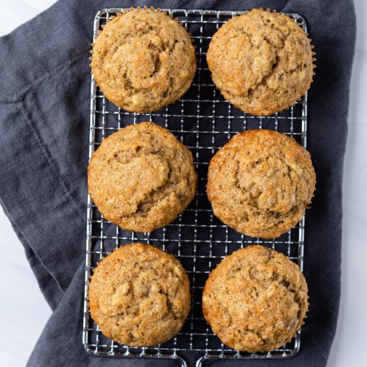 overhead of six banana muffins on a wire rack with blue napkin underneath