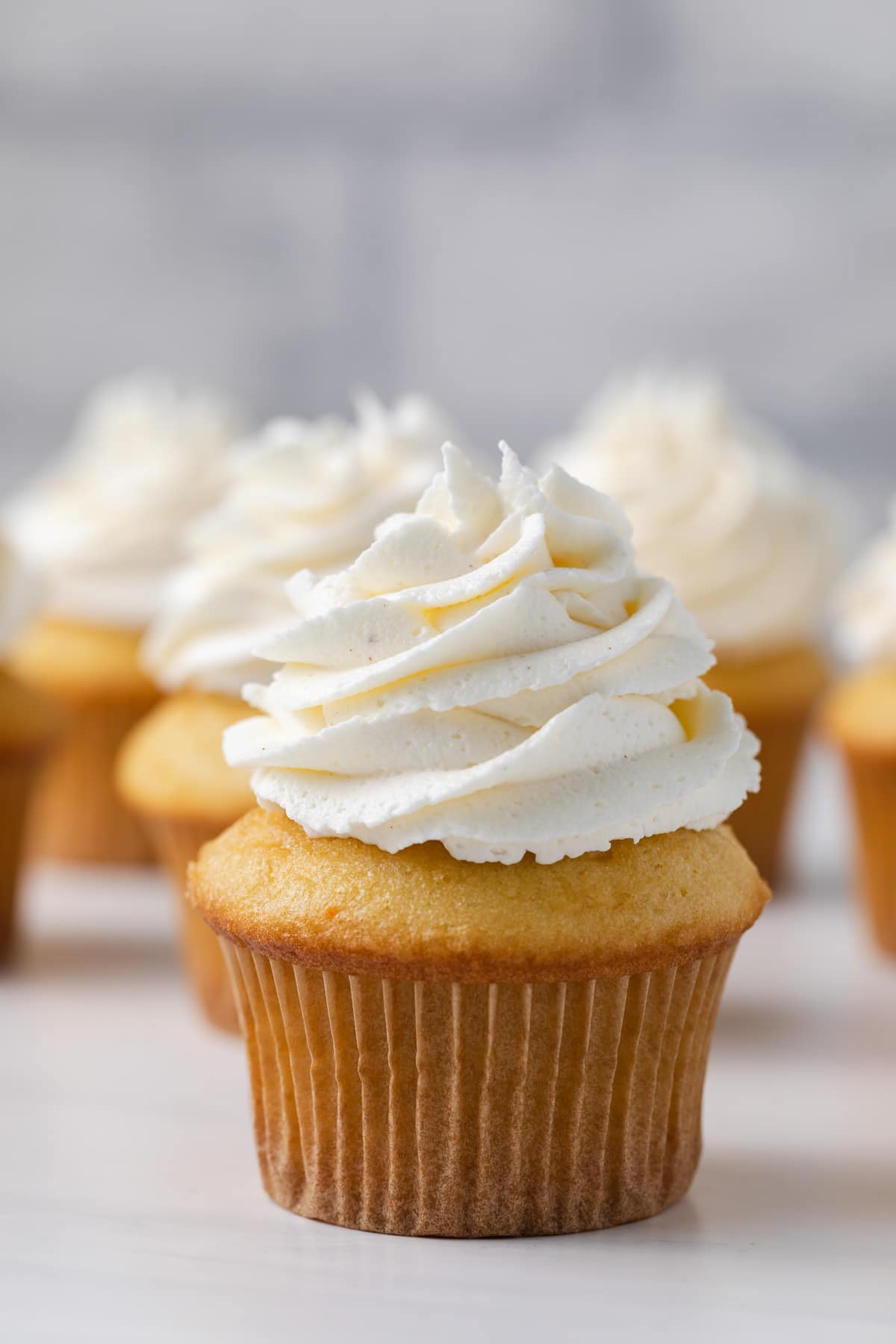side view of yellow cupcake topped with a fluffy swirl of brown butter frosting