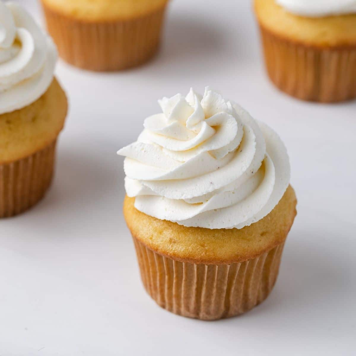angled view of brown butter frosting swirled over yellow cupcakes