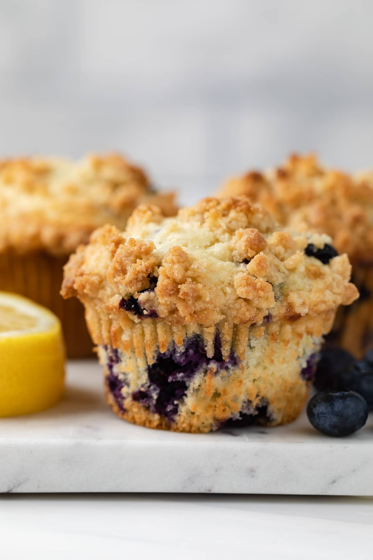 side view a muffin dotted with blueberries on a marble slab