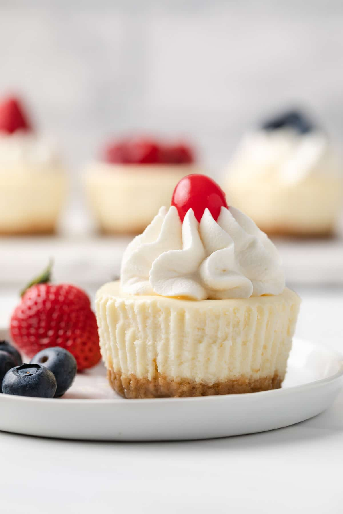 mini cheesecake topped with whipped cream and a cherry on a white plate