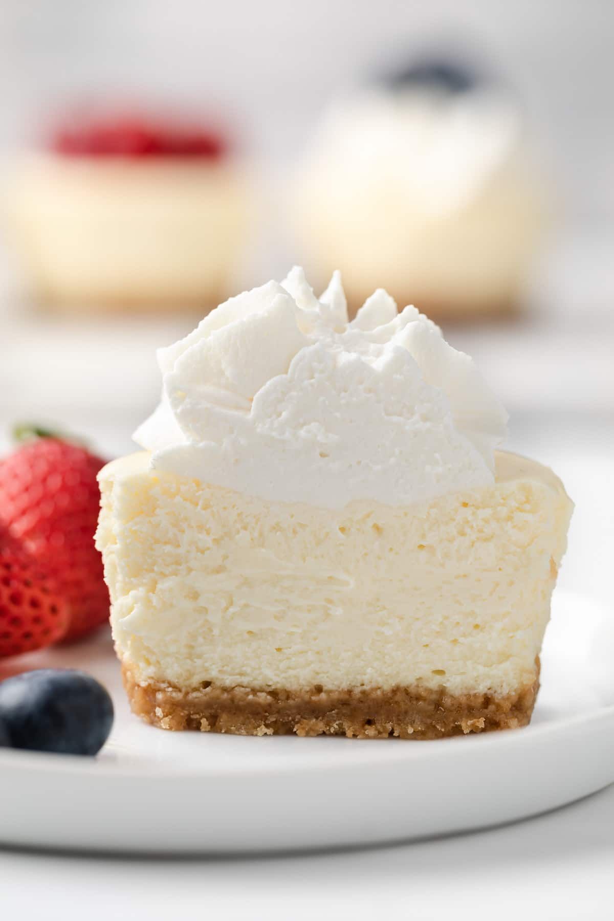 close up of mini cheesecake sliced so the creamy inside is visible