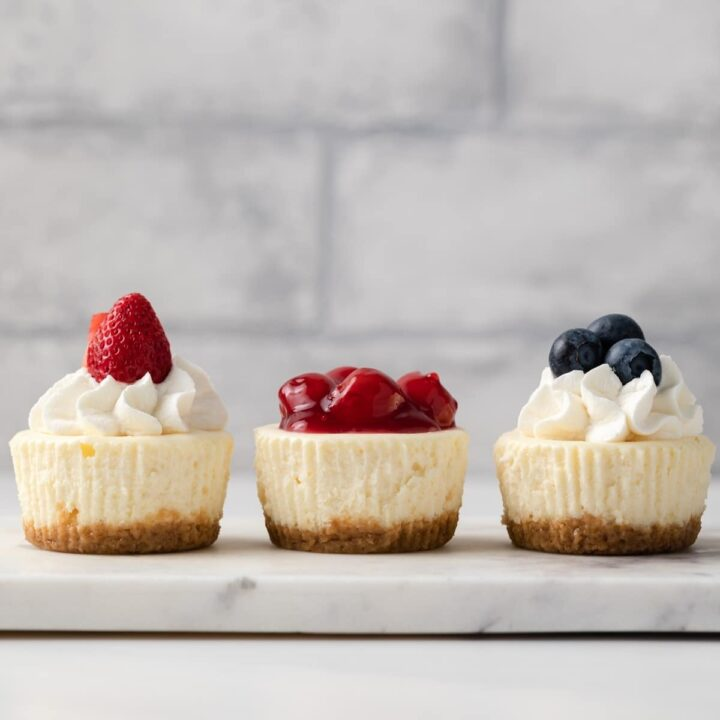 three mini cheesecakes topped with whipped cream and fruit on a marble platter