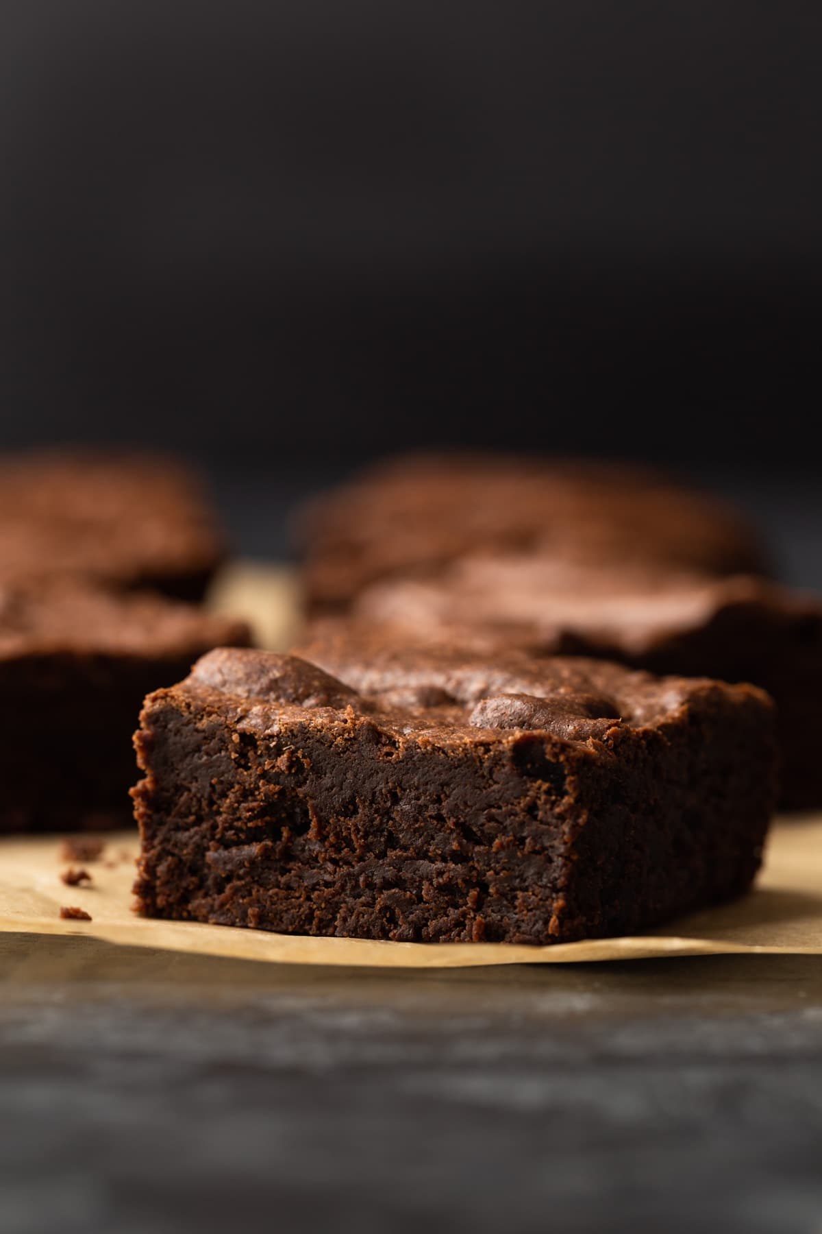 one chocolate brownie sitting on brown parchment paper