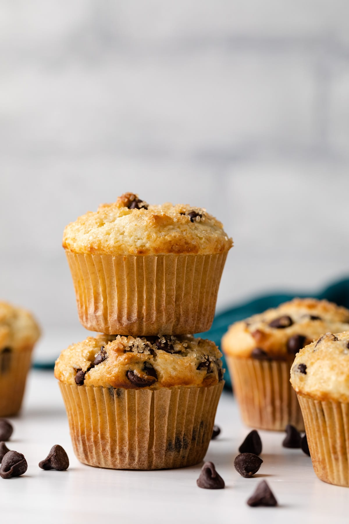 two chocolate chip muffins stacked with more muffins and chocolate chips scattered around