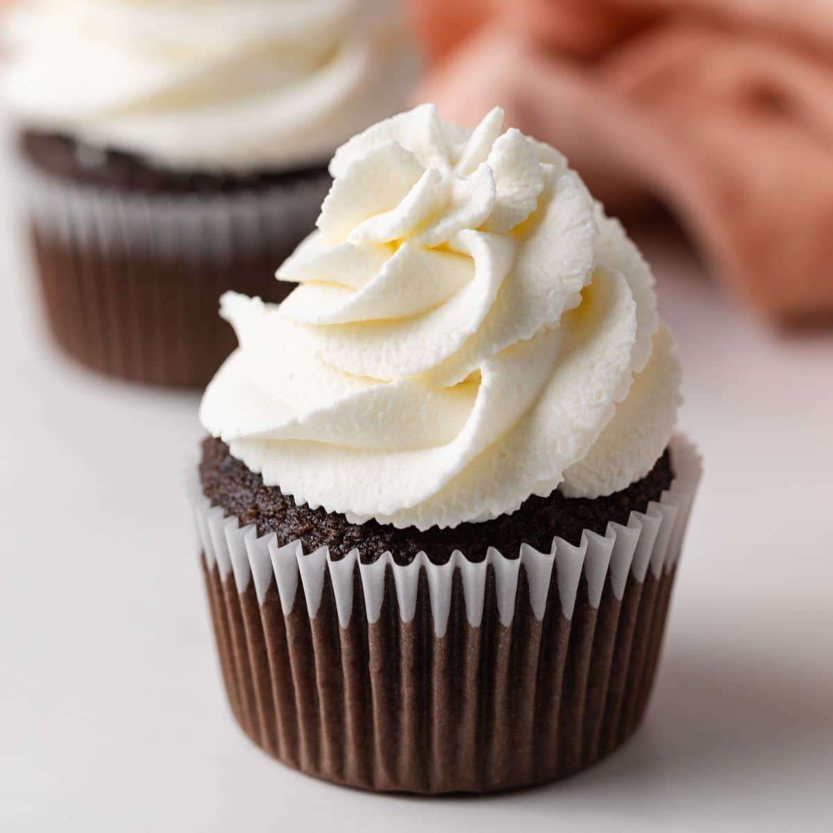 whipped cream swirled on top of chocolate cupcakes