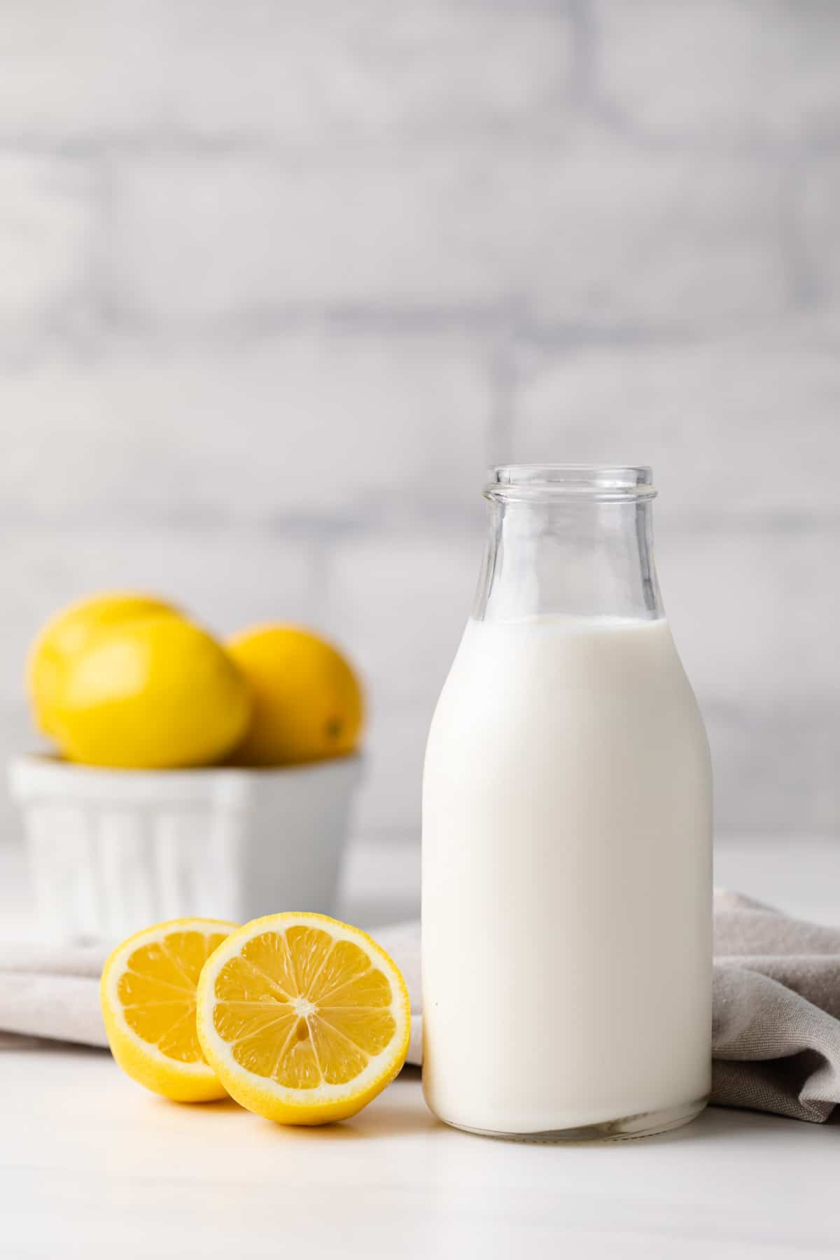 glass jar filled with homemade buttermilk along with a napkin and lemons in the background