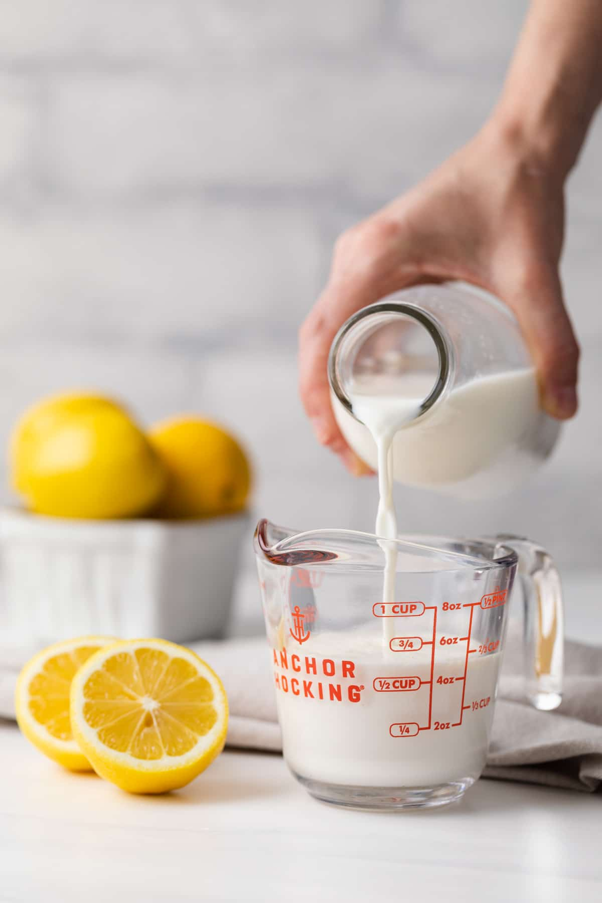 a glass measuring cup being filling with milk along with lemons and napkin in background