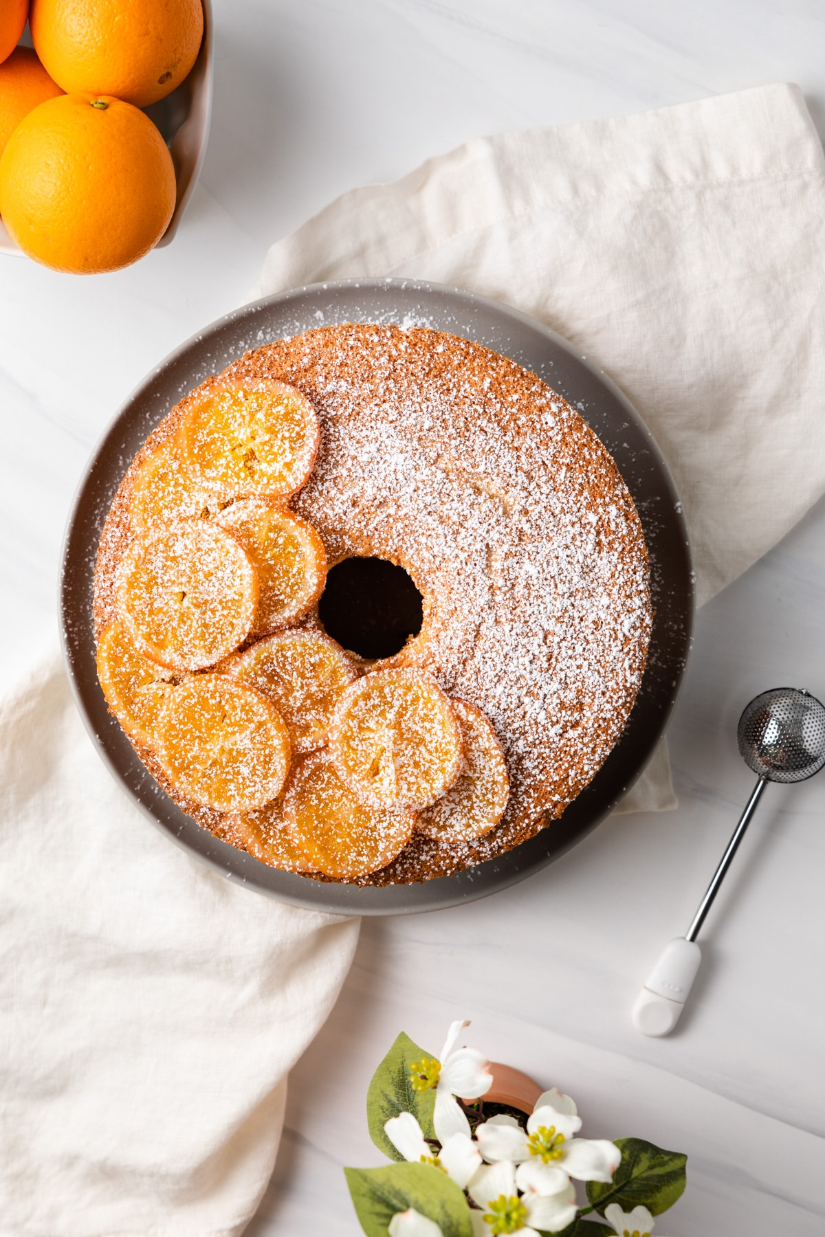 overhead of orange chiffon cake decorated with candy orange slices and powdered sugar
