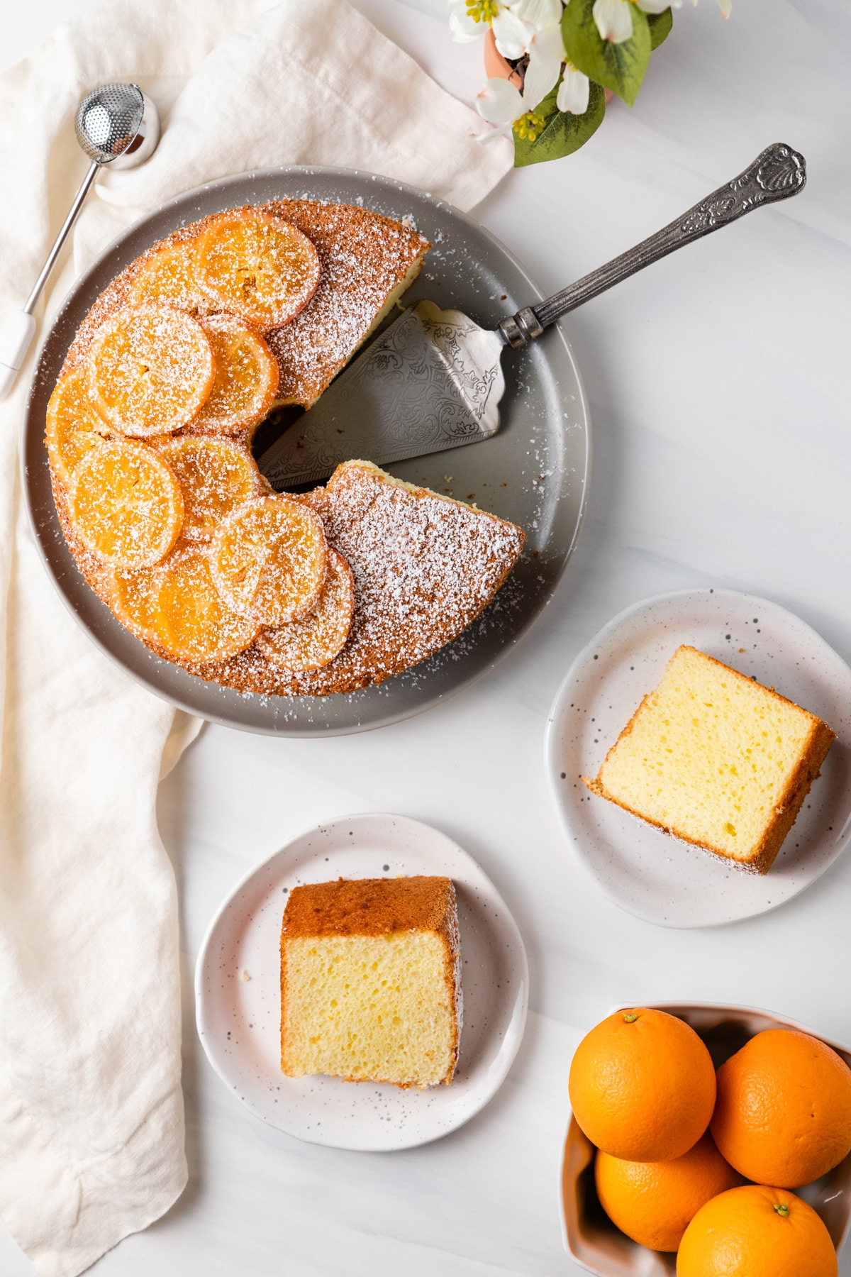 overhead of orange chiffon cake next to two slices on plates