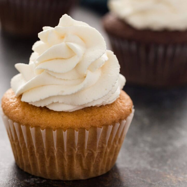 whipped cream swirled over a vanilla cupcake with chocolate cupcakes in the background