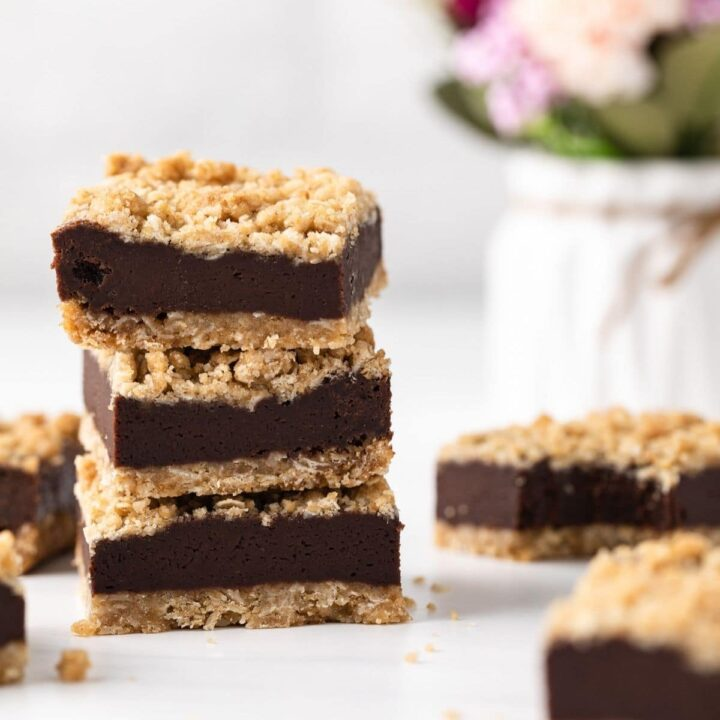 three chocolate oatmeal bars stacked next to flowers in vase and more oat bars