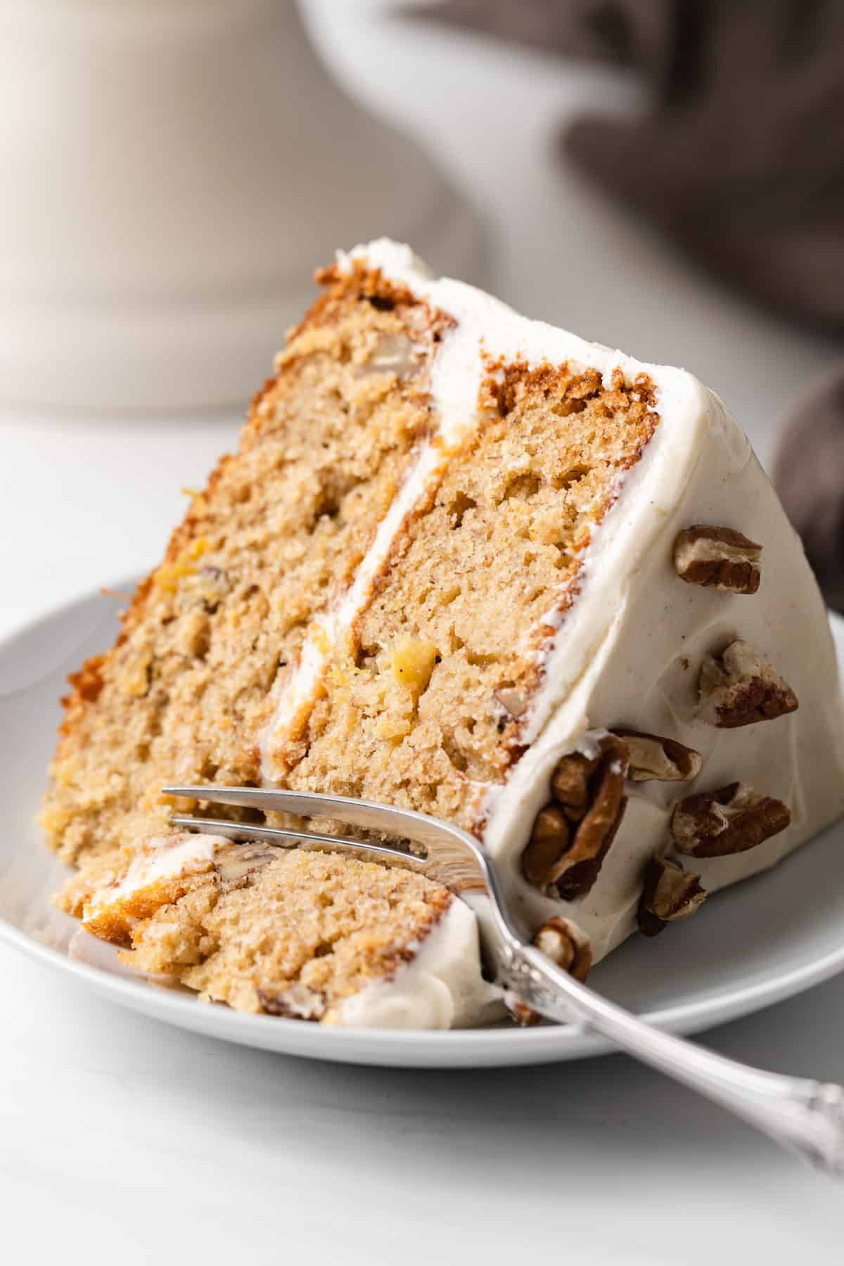 slice of hummingbird cake with fork taking a bite out