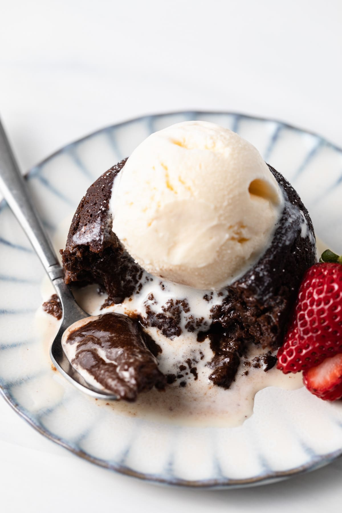 angled view of lava cake topped with ice cream and a spoon taking a bite out