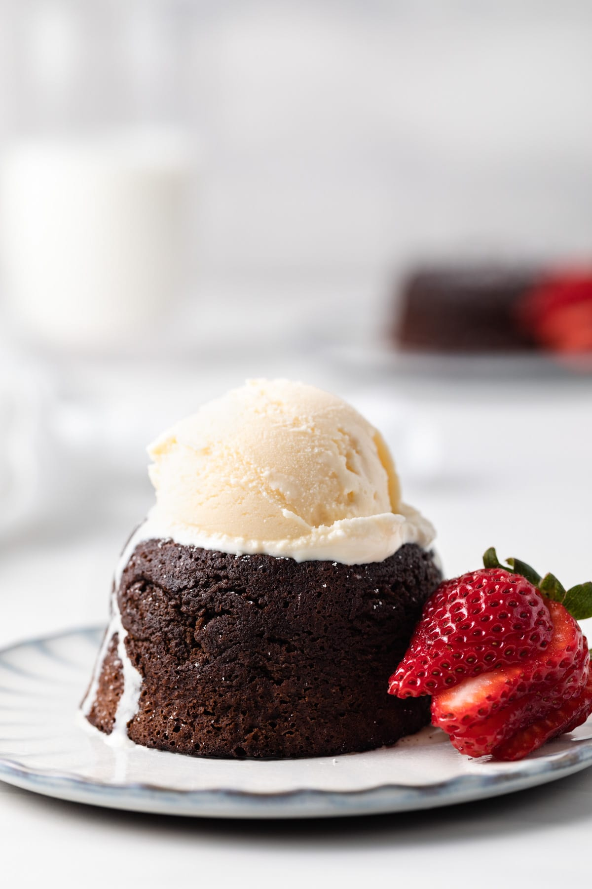 side view of individual molten lava cake with scoop of ice cream on top