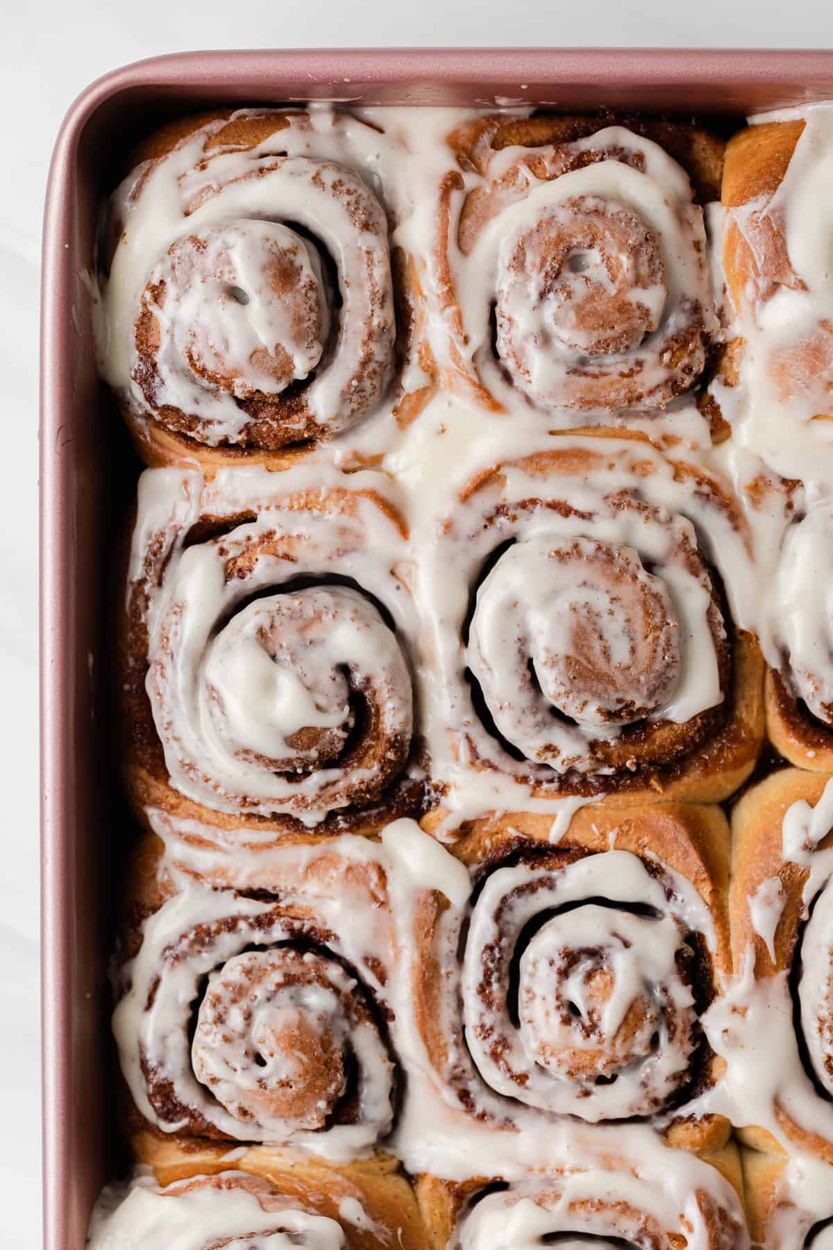 overhead of iced cinnamon rolls in a pink baking pan