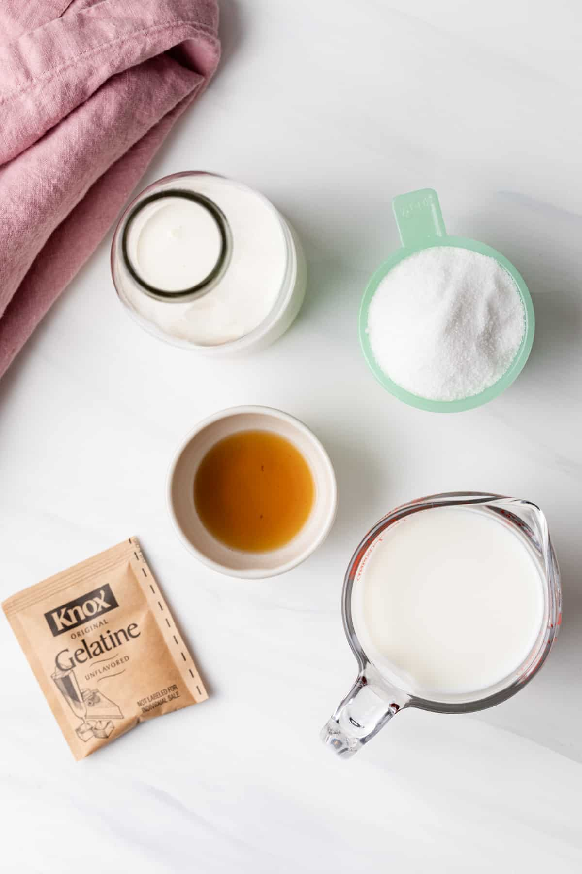 Milk in a glass measuring cup, cream in a glass jar, sugar in a jade measuring cup, vanilla in a cream bowl, and a packet of gelatin powder
