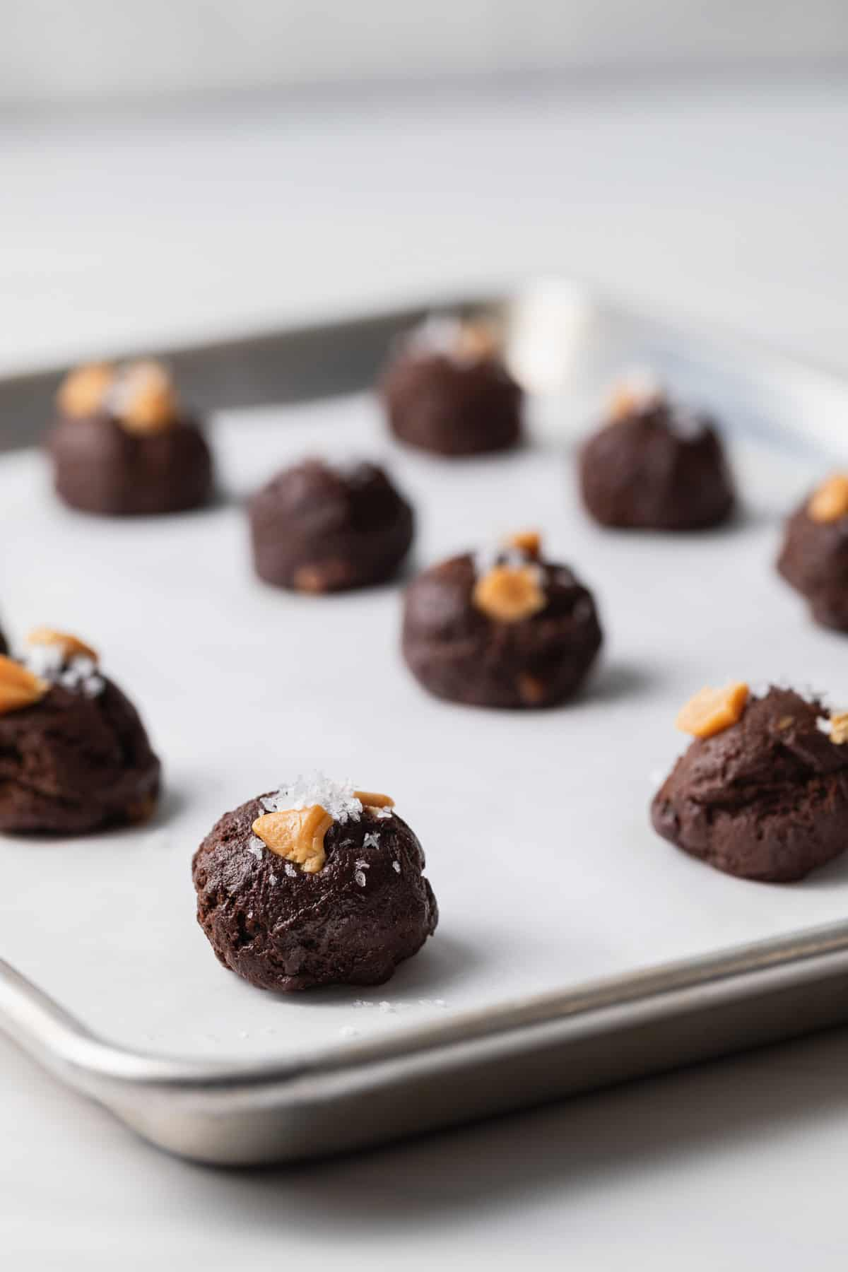 unbaked brownie cookies on a baking sheet lined with parchment paper