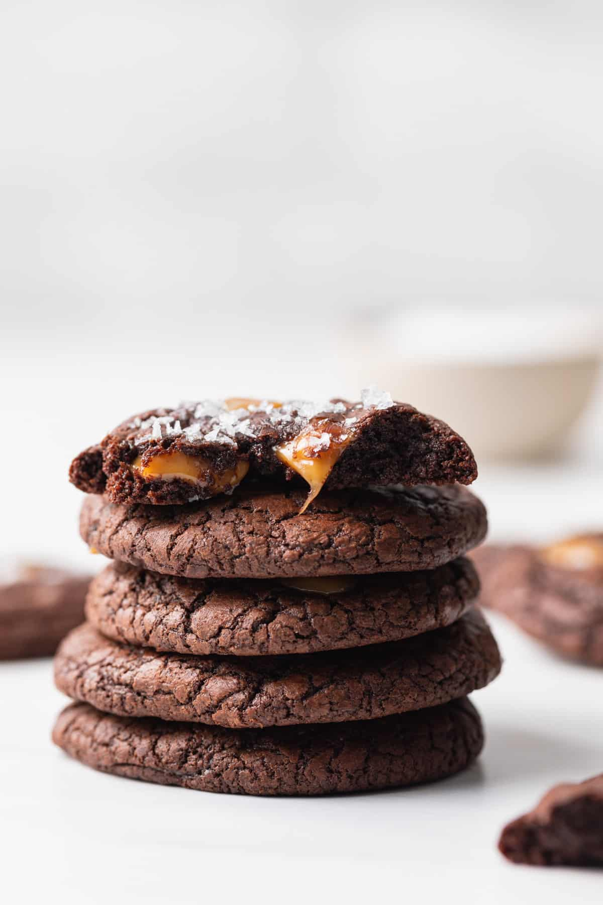 five salted caramel brownie cookies stacked with the top one broken in half so the gooey caramel is visible