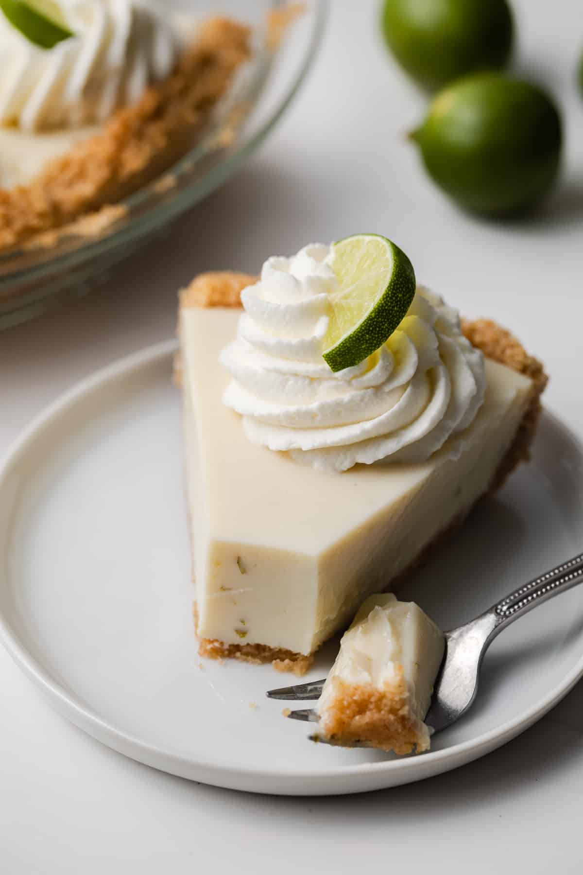 angled view of slice of key lime pie with fork taking a bite out