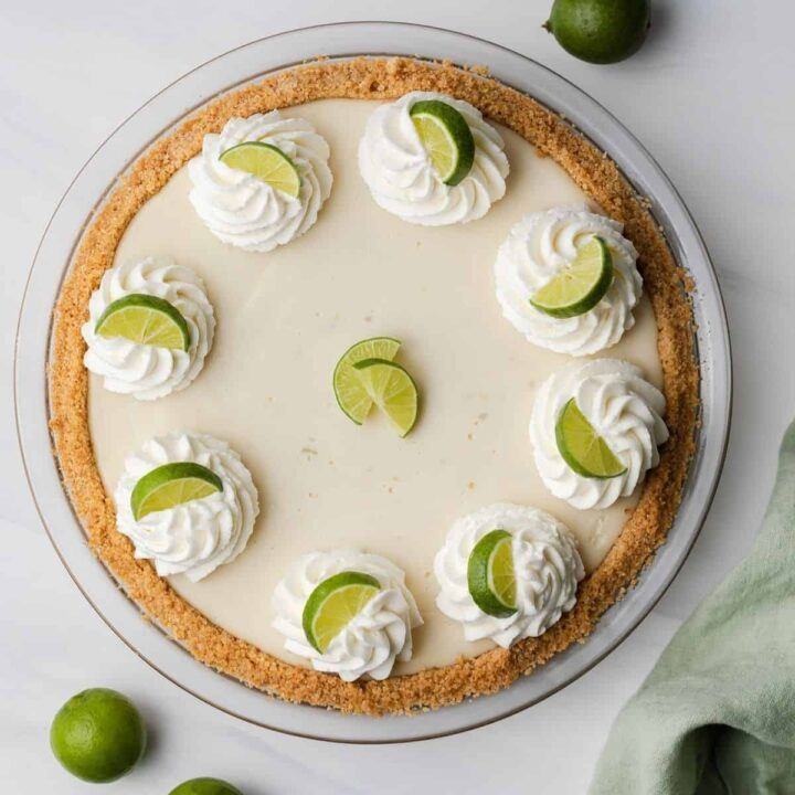 overhead of key lime pie topped with whipped cream swirls and lime slices