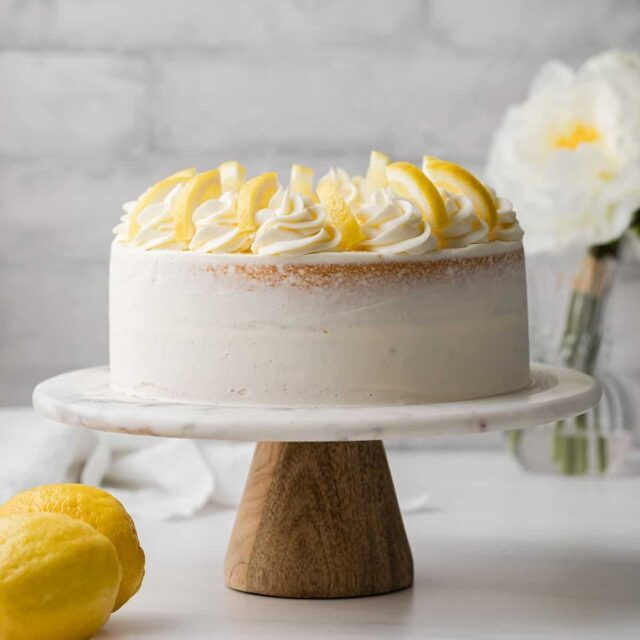 lemon cake on a marble cake stand with wooden bottom, flowers in the background, and l two lemons in the foreground