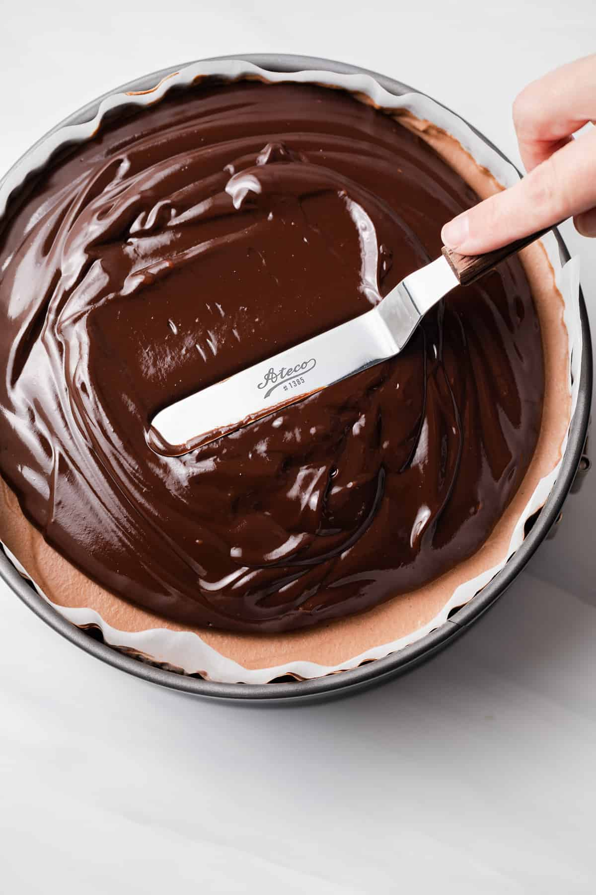 Ganache spread over mousse cake in pan.