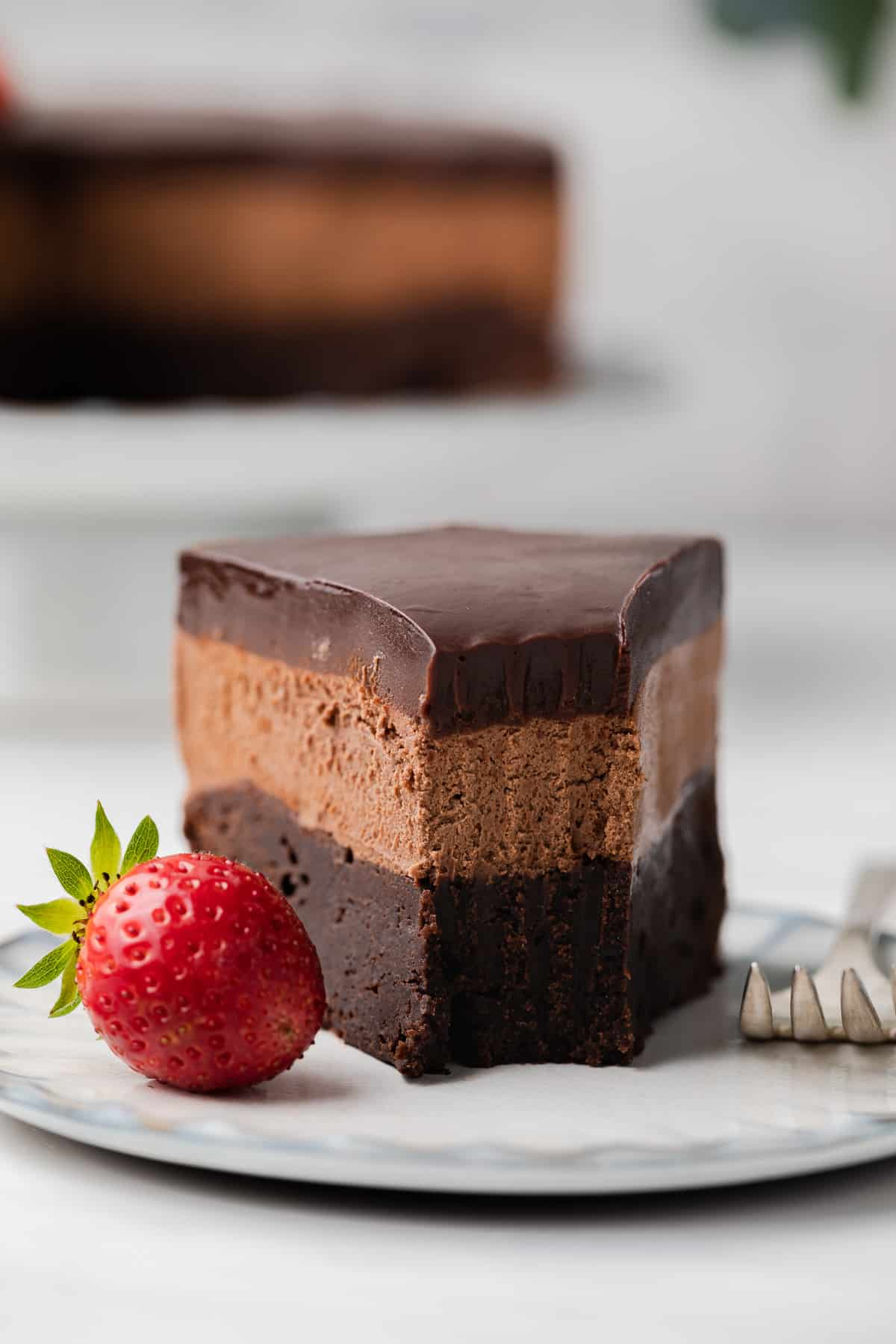Slice of three layer mousse cake on white plate with a bite taken out.